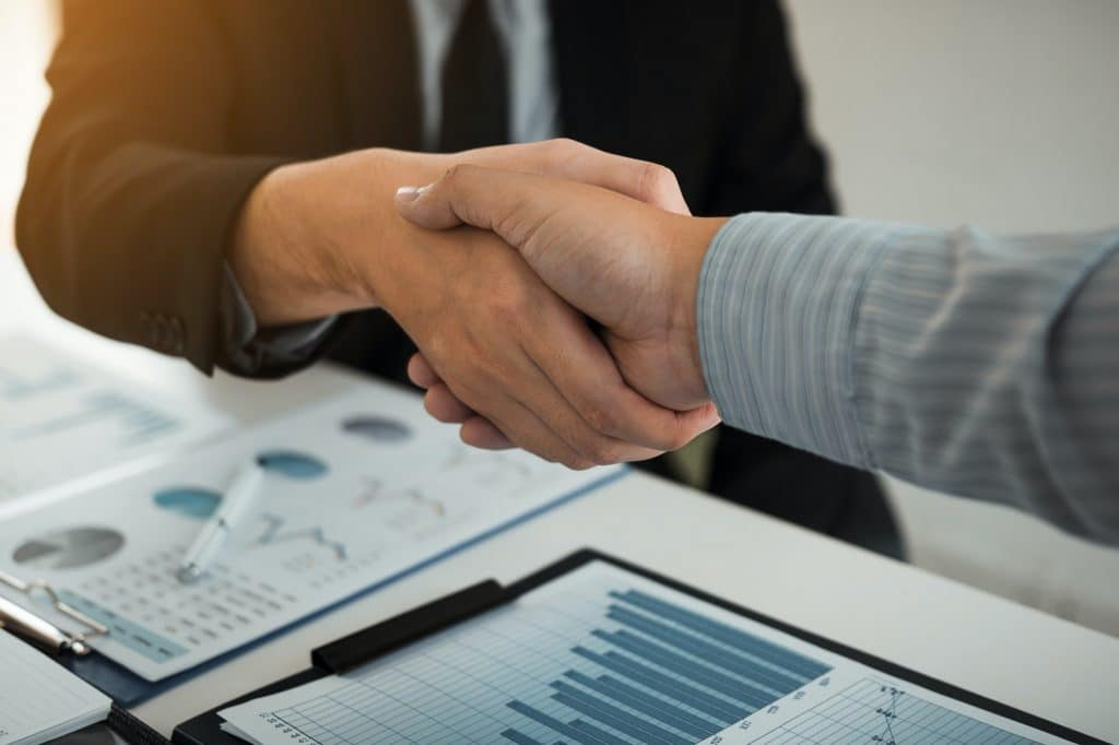 Business partnership shaking hands for signing company.