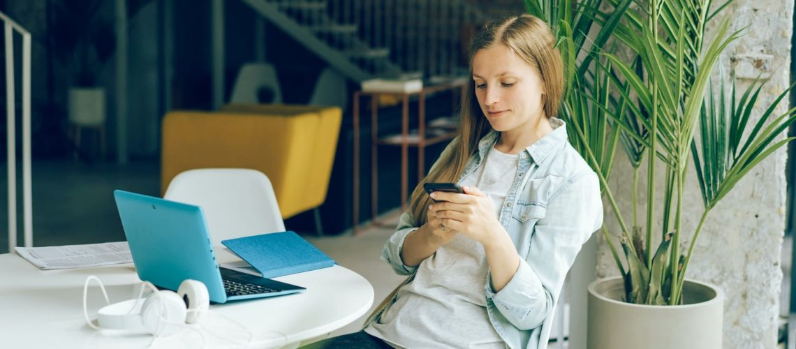 A woman looks on the screen of phone, using social media. Remote work and distance learning.